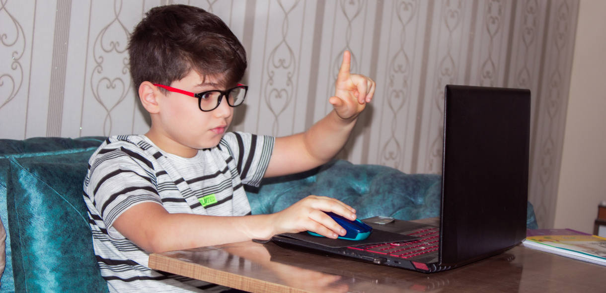 young boy wearing glasses is sitting at a table working on a laptop with his hand raised and index finger extended